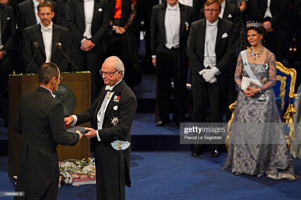 Nobel Laureate Professor Shinya Yamanaka of Japan receives the 2012 Nobel Prize for Medicine from King Carl XVI Gustaf of Sweden as Queen Silvia of...