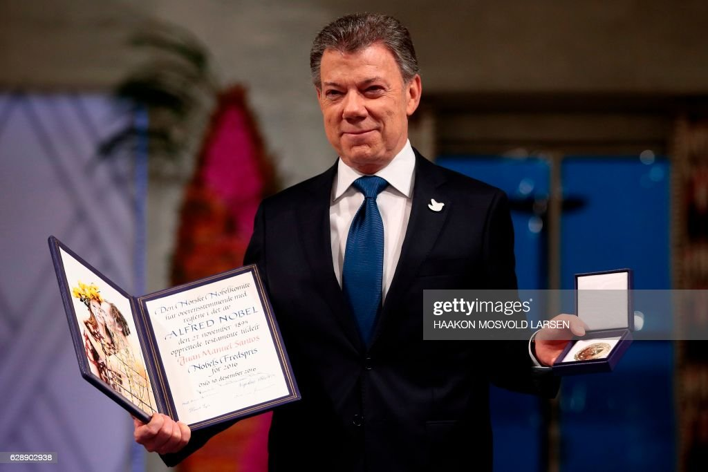 TOPSHOT - Nobel Peace Prize laureate Colombian President Juan Manuel Santos poses with the medal and diploma during the award ceremony of the Nobel Peace Prize on December 10, 2016 in Oslo, Norway. Colombian President Juan Manuel Santos was awarded this year's Nobel Peace Prize for his efforts to bring Colombia's more than 50-year-long civil war to an end. / AFP / NTB SCANPIX / Haakon Mosvold Larsen / Norway OUT