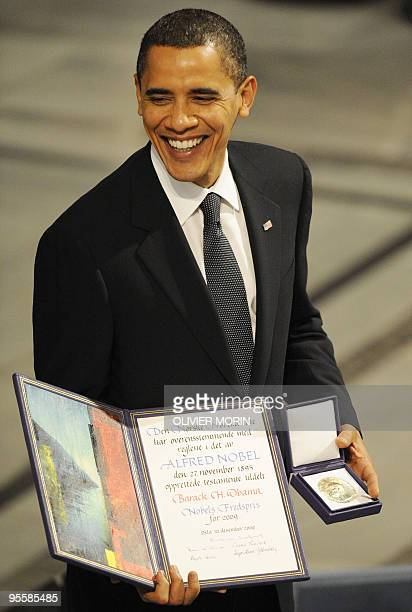 Nobel Peace Prize laureate US President Barack Obama poses on the podium with his diploma and gold medal during the Nobel ceremony at the City Hall...