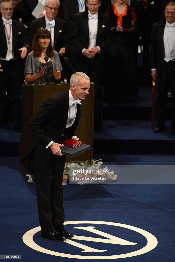 Nobel Prize in Chemistry laureate Professor Brian K. Kobilka of the USA (L) reacts after he received his Nobel Prize from King Carl XVI Gustaf of Sweden during the 2012 Nobel Prize Award Ceremony during the Nobel Prize Ceremony at Concert Hall on December 10, 2012 in Stockholm, Sweden.