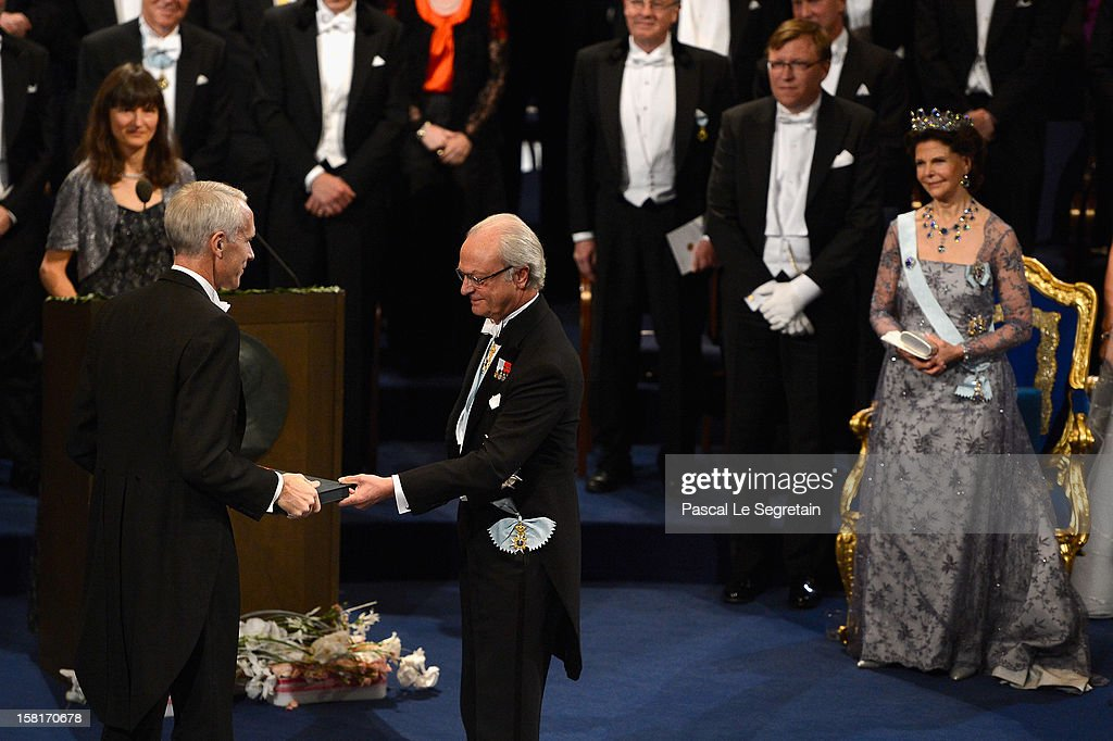 Nobel Prize in Chemistry laureate Professor Brian K. Kobilka of the USA (L) receives his Nobel Prize from King Carl XVI Gustaf of Sweden (C) as <a gi-track='captionPersonalityLinkClicked' href=/galleries/search?phrase=Queen+Silvia+of+Sweden&family=editorial&specificpeople=160332 ng-click='$event.stopPropagation()'>Queen Silvia of Sweden</a> (R) looks on, during the 2012 Nobel Prize Award Ceremony during the Nobel Prize Ceremony at Concert Hall on December 10, 2012 in Stockholm, Sweden.
