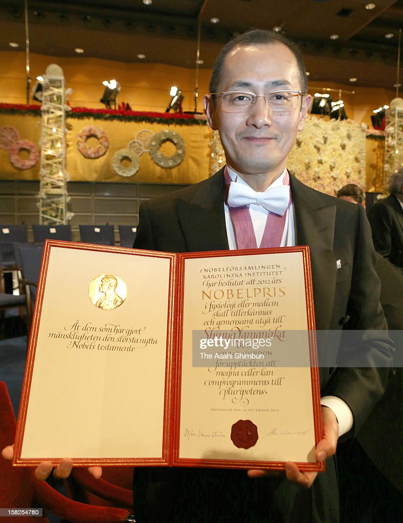 Nobel Prize in Medicine laureate Shinya Yamanaka poses for photographs with his award certificate after the award ceremony at Concert Hall on...