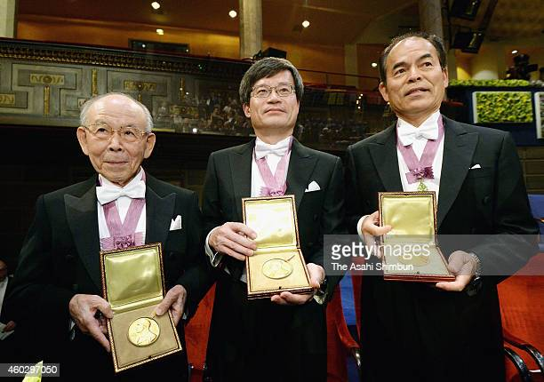 Nobel Prize in Physics winners Isamu Akasaki Hiroshi Amano and Shuji Nakamura display their medals after the Nobel Prize Awards Ceremony at Concert...