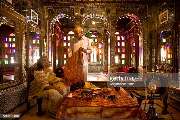 Nobleman Nahar Singhji also known as Rao Saheb stands in discussion with his wife Rani Saheb in the Sheesh Mahal suite of Deogarh Mahal a 340 year...