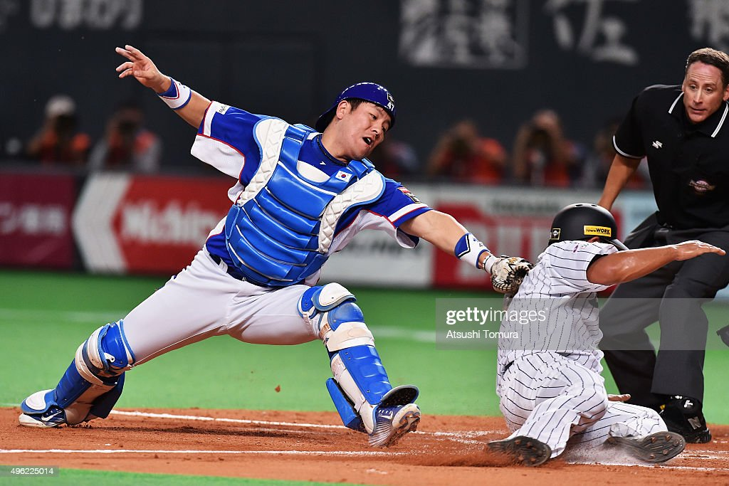 Nobuhiro Matsuda of Japan slides safely into the home by a sacrifice fly of Hayato Sakamoto while catcher Kang Minho of South Korea tries to tag in...