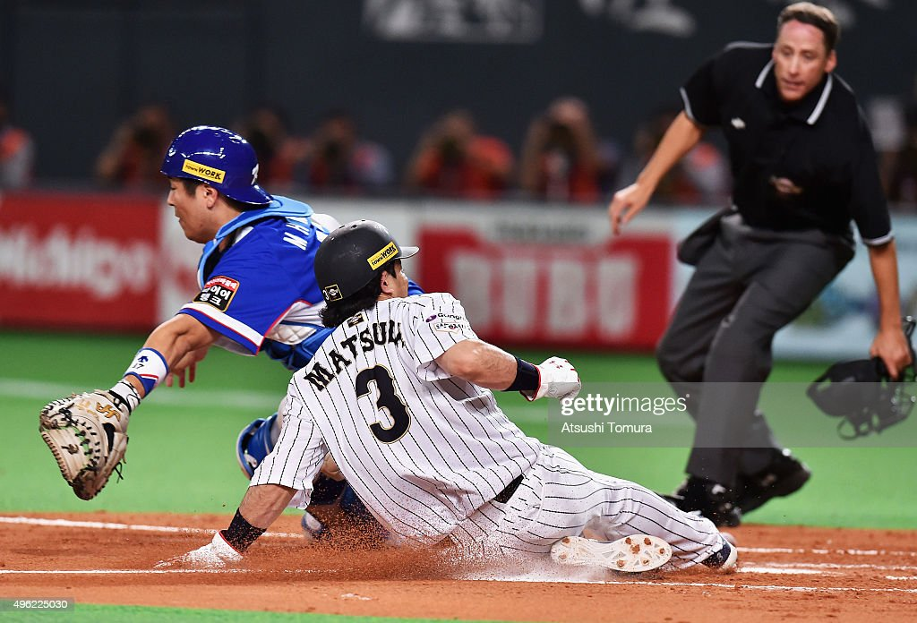 Nobuhiro Matsuda #3 of Japan slides safely into the home to score by a sacrifice fly of Hayato Sakamoto #6 while catcher Kang Minho #47 of South Korea tries to tag in the bottom of second inning during the WBSC Premier 12 match between Japan and South Korea at the Sapporo Dome on November 8, 2015 in Sapporo, Hokkaido, Japan.