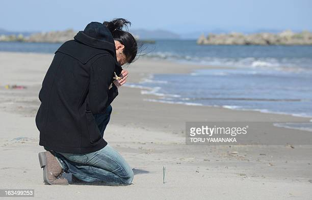 Nobuhiro Narita prays for his friend killed by the tsunami at Arahama district in Sendai Miyagi Prefecture on March 11 2013 Japan on March 11 marked...