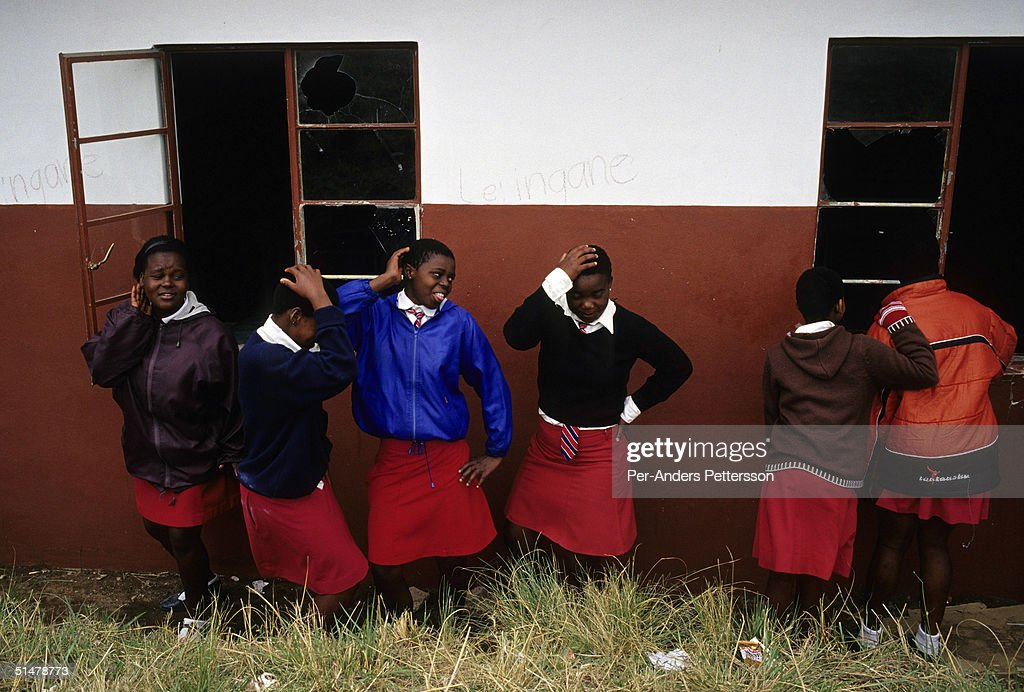 Nobule Ngema dances with her friends outside the classroom of their high school on September 10 2004 in Ngudwini village in rural Natal South Africa...