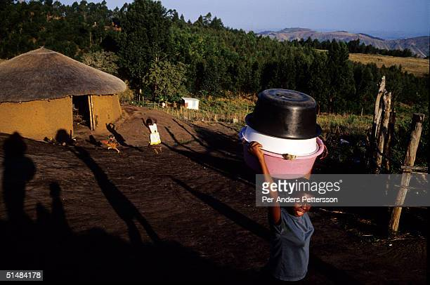 Nobule Ngema walks to a nearby river to wash clothes as she prepares to travel to the annual Reed Dance on September 10 2004 in Ngudwini village in...