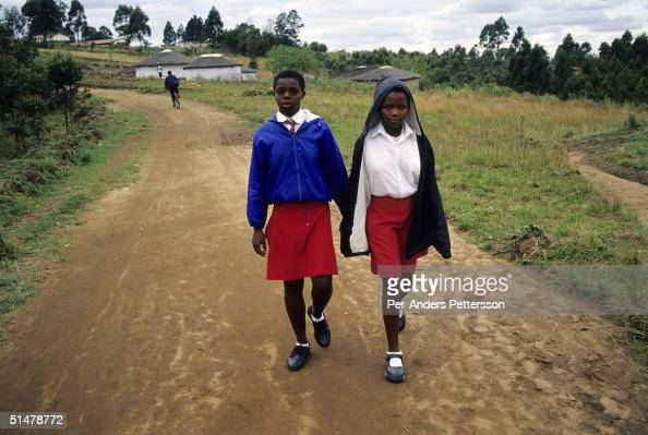 Nobule Ngema walks with a friend to her high school on September 10 2004 in Ngudwini village in rural Natal South Africa She's preparing to travel to...