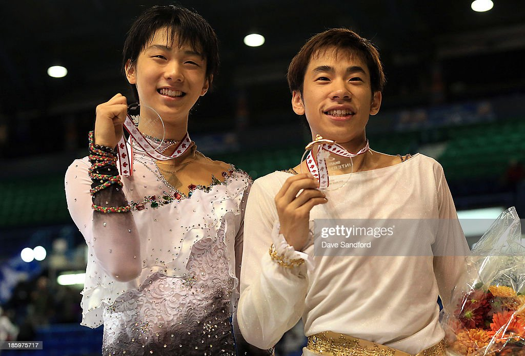 Nobunari Oda (R) of Japan celebrates his bronze medal win with Yuzuru Hanyu of Japan who took the silver in the men's free program on day two at the ISU GP 2013 Skate Canada International at Harbour Station on October 26, 2013 in Saint John, New Brunswick, Canada.