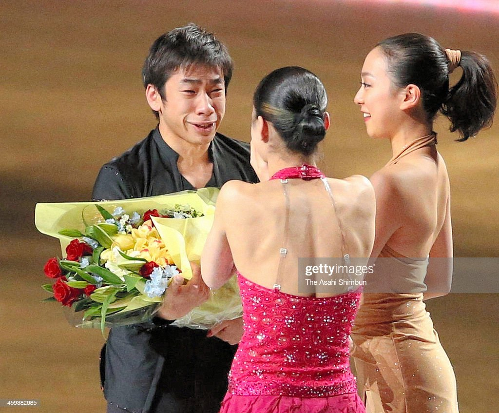 Nobunari Oda (L) receives a flower bunch from Kanako Murakami (C) and Mao Asada (R) during the gala exhibition as he announced the retirement during day four of the 82nd All Japan Figure Skating Championships at Saitama Super Arena on December 24, 2013 in Saitama, Japan.