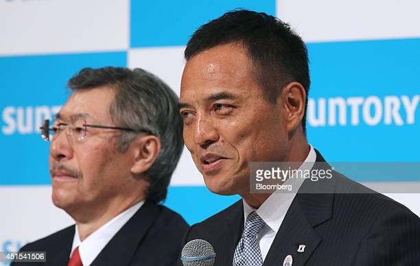 Nobutada Saji chairman and chief executive officer of Suntory Holdings Ltd left listens as Takeshi Niinami incoming president of the company speaks...