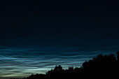 Noctilucent clouds or night shining clouds in the dark night sky. Noctilucent clouds consist of ice crystals and are only visible during twilight.