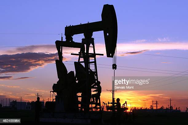 A CNPC 'nodding donkey' oil pump at sunset in an oilfield on July 13 2006 in outside Daqing Heilongjiang province China China National Petroleum Corp...