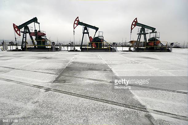 Nodding donkey oil pumps operated by Moravske Naftove Doly as work against a background of gas storage tanks in Uhrice Czech Republic on Wednesday...