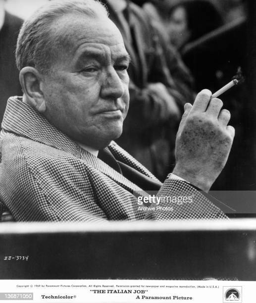 Noel Coward sitting holding a cigarette in a scene from the film 'The Italian Job' 1969