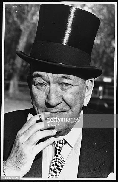 Noel Coward smokes a cigarette after the Queen awards him with a knighthood