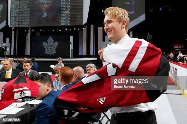 Noel Hoefenmayer puts on the Arizona Coyotes jersey after being selected 108th overall during the 2017 NHL Draft at the United Center on June 24 2017...