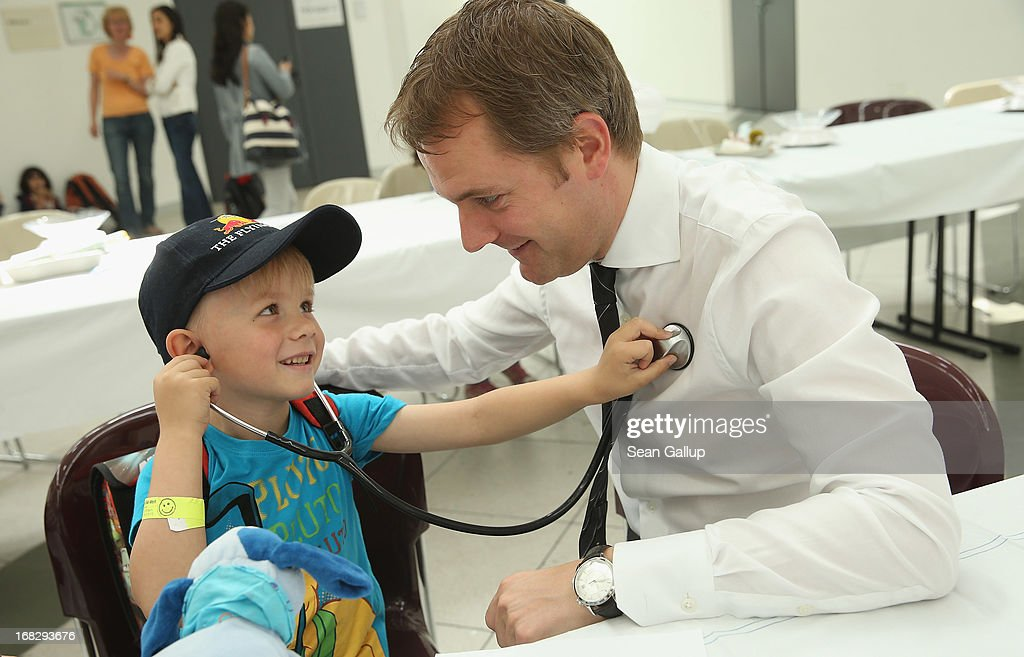 Noel, 6, listens for the heartbeat of German Health Minister <a gi-track='captionPersonalityLinkClicked' href=/galleries/search?phrase=Daniel+Bahr&family=editorial&specificpeople=7622444 ng-click='$event.stopPropagation()'>Daniel Bahr</a> (R) at the Teddy Bear Clinic at Charite Hospital on May 8, 2013 in Berlin, Germany. Charite Hospital hosts the annual Teddy Bear Clinic days and invites children from Berlin day care centers to bring their injured teddy bears for fictitious examinations, x-rays, surgery and healing as a way for small children to become acquainted with a medical environment.