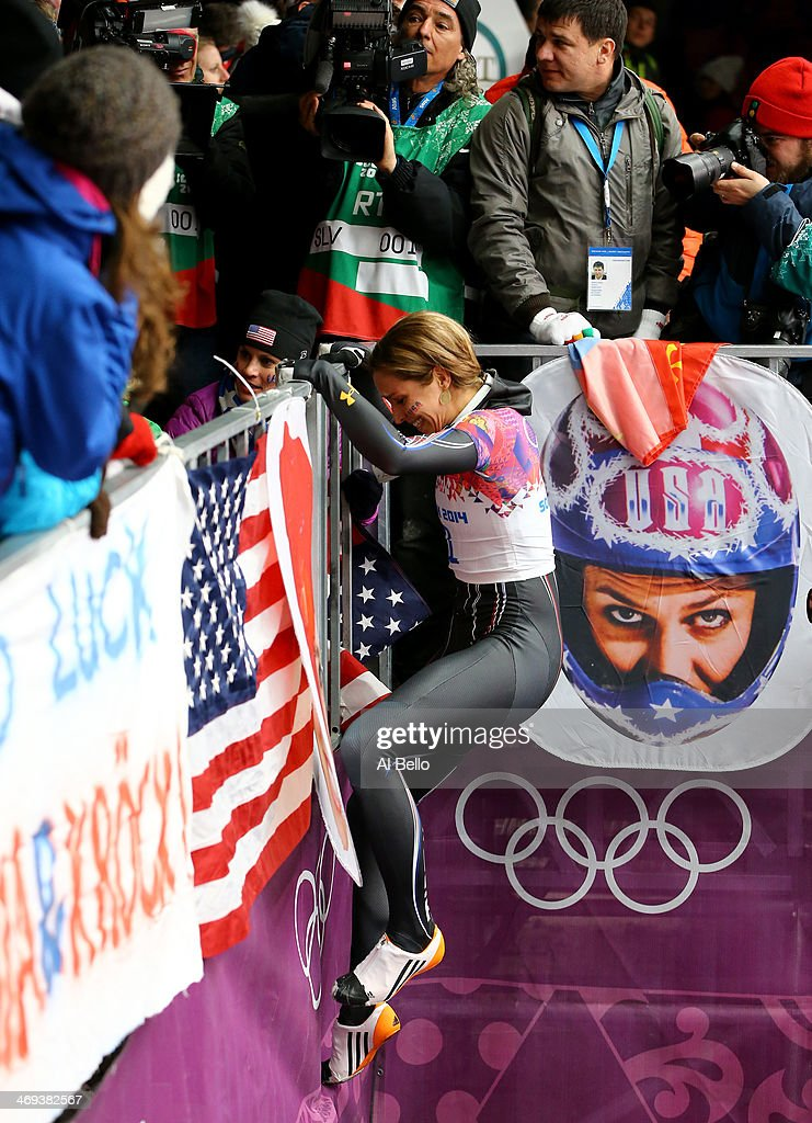 Noelle PikusPace of the United States climbs the fence to meet her family after winning the silver medal during the Women's Skeleton on Day 7 of the...