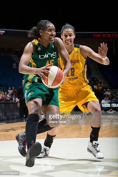 Noelle Quinn of the Seattle Storm drives past Nicole Powell of the Tulsa Shock during the WNBA game on June 22 2013 at the BOK Center in Tulsa...
