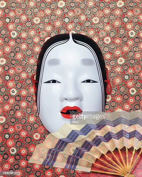 Noh mask and Japanese folding fan spreading out, front view, composition
