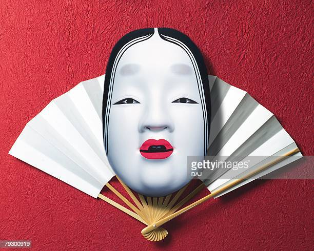 Noh mask on Japanese folding fan, front view, red background
