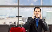 Portrait of businessman covering his ears with hand to not hear the great noise at the airport