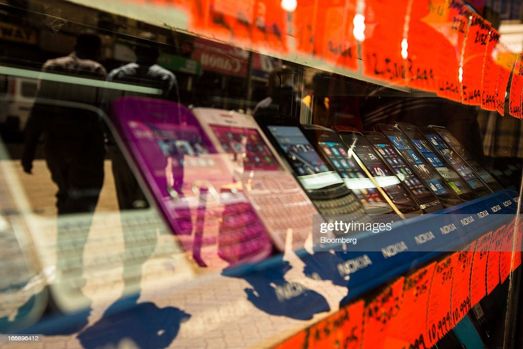 Nokia Asha mobile handsets sit on display in the window of a phone store in Nairobi, Kenya, on Wednesday, April 17, 2013. Though only 23 percent of houses there have electricity and just 9 percent of roads are paved, mobile-phone penetration is 75 percent in the country, up from 5 percent in 2003. Photographer: Trevor Snapp/Bloomberg via Getty Images