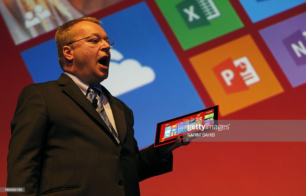 Nokia CEO, Canadian Stephen Elop, holds a Nokia Lumia 2520 on stage during an event to unveil Nokia's latest products on October 22, 2013 in Abu Dhabi. Nokia has unveiled its first phablets -extra-large phones- and its first tablet computer. AFP PHOTO / KARIM SAHIB