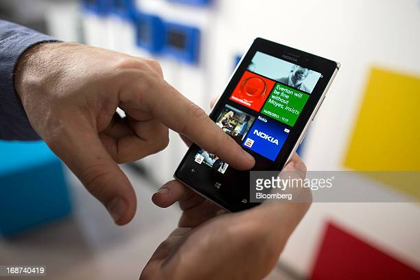 A Nokia Oyj employee demonstrates a Nokia Lumia 925 Windows Phone during the launch of the mobile handset in London UK on Tuesday May 2013 Nokia Oyj...