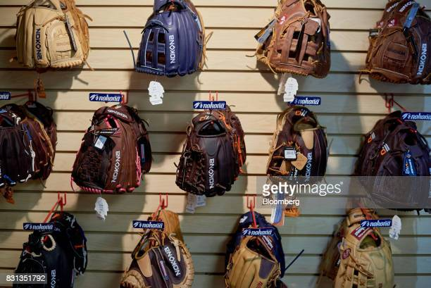 Nokona baseball and softball gloves hang on display for sale inside the store at the company's manufacturing facility in Nocona Texas US on Thursday...