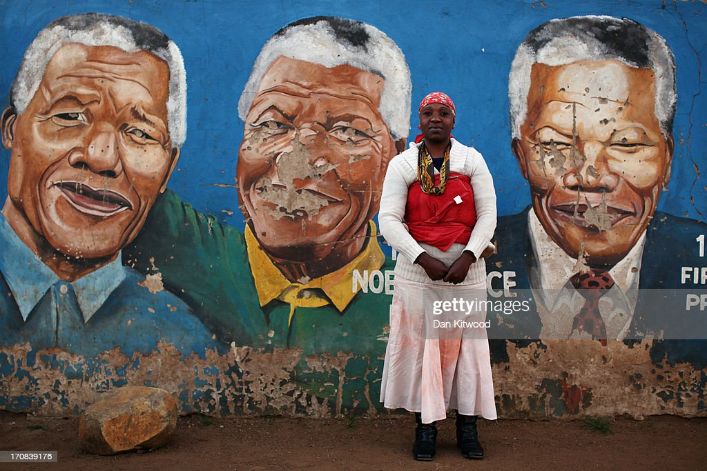 Nokuthula Mbonde, 30, poses for a portrait by a mural of Nelson Mandela in Soweto on June 14, 2013 in Johannesburg, South Africa. Speaking of Nelson Mandela Ms Siqangwe said, 'He means a lot, he means freedom'. The former South African President and leader of the anti-apartheid movement has spent over a week in hospital after being admitted for a recurring lung infection.