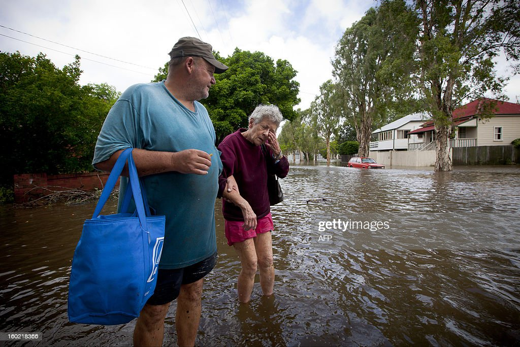 Nola McAlpine (R), 76, reacts as her son Evan assists her through floodwaters as they evacuate from their Cullen Street home in the inner Brisbane suburb of Newmarket on January 28, 2013. Helicopters plucked dozens of stranded Australians to safety in dramatic rooftop rescues on January 28 as severe floods swept the northeast, killing three people and inundating thousands of homes. AFP PHOTO / Patrick HAMILTON