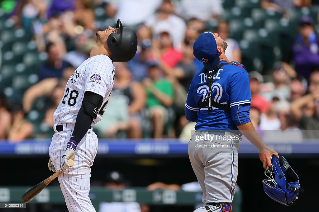 <a gi-track='captionPersonalityLinkClicked' href=/galleries/search?phrase=Nolan+Arenado&family=editorial&specificpeople=7934273 ng-click='$event.stopPropagation()'>Nolan Arenado</a> #28 of the Colorado Rockies and catcher <a gi-track='captionPersonalityLinkClicked' href=/galleries/search?phrase=Josh+Thole&family=editorial&specificpeople=5741573 ng-click='$event.stopPropagation()'>Josh Thole</a> #22 of the Toronto Blue Jays look towards the sky as Arenado pops out to end the eighth inning at Coors Field on June 29, 2016 in Denver, Colorado. The Blue Jays defeated the Rockies 5-3.