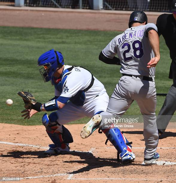 Nolan Arenado of the Colorado Rockies beats the throw to Yasmani Grandal of the Los Angeles Dodgers to score a run in the game at Dodger Stadium on...