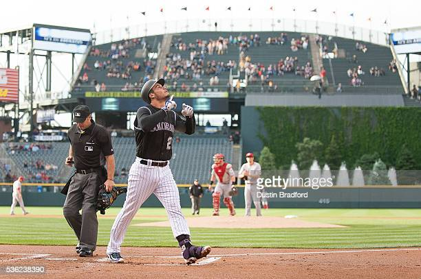 Nolan Arenado of the Colorado Rockies celebrates after hitting a first inning tworun home run off of Jon Moscot of the Cincinnati Reds at Coors Field...