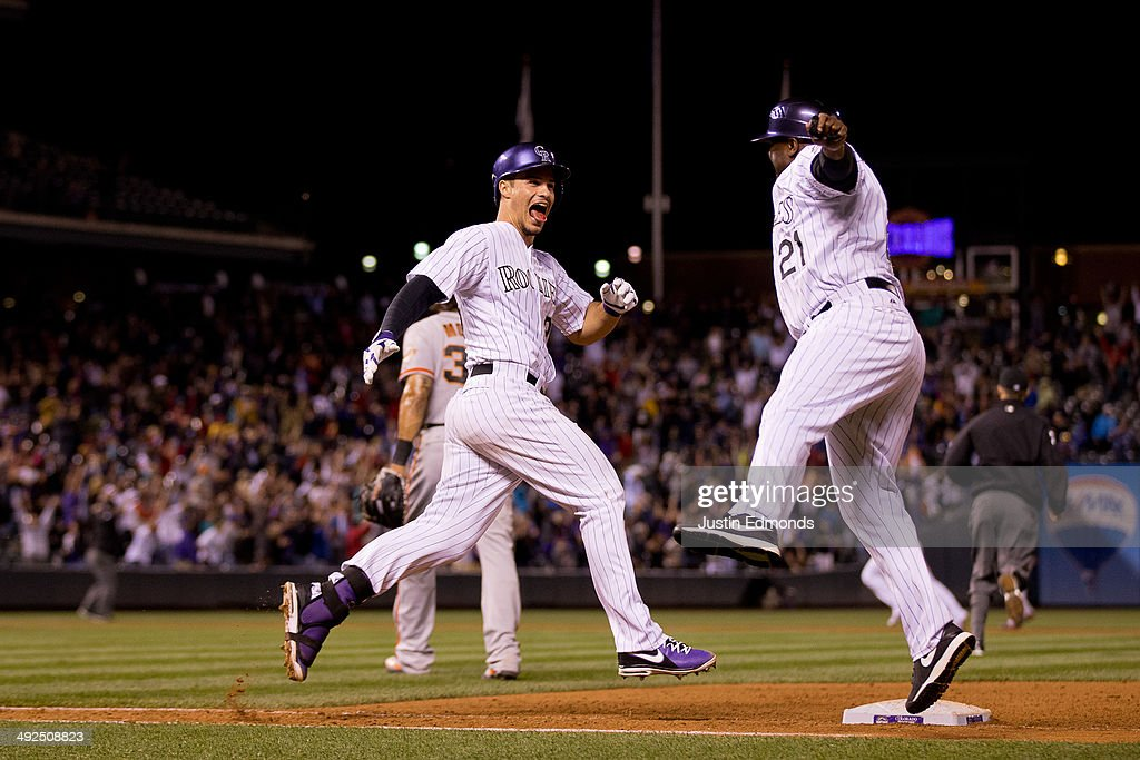 Nolan Arenado #28 of the Colorado Rockies celebrates his walk off single that scored two runs with first base coach Eric Young #21 as the Rockies defeated the San Francisco Giants 5-4 at Coors Field on May 20, 2014 in Denver, Colorado.