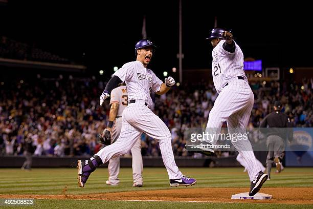 Nolan Arenado of the Colorado Rockies celebrates his walk off single that scored two runs with first base coach Eric Young as the Rockies defeated...