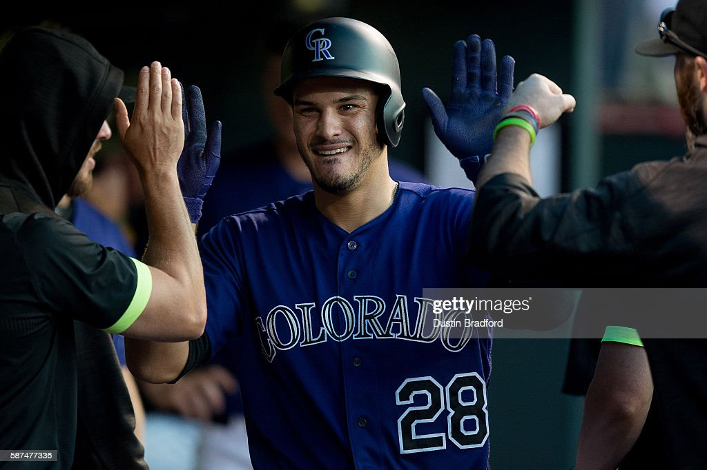 Nolan Arenado #28 of the Colorado Rockies celebrates in the dugout after hitting a fourth inning solo homerun, the 100th of his MLB career, off of Cole Hamels #35 of the Texas Rangers during a game at Coors Field on August 8, 2016 in Denver, Colorado.