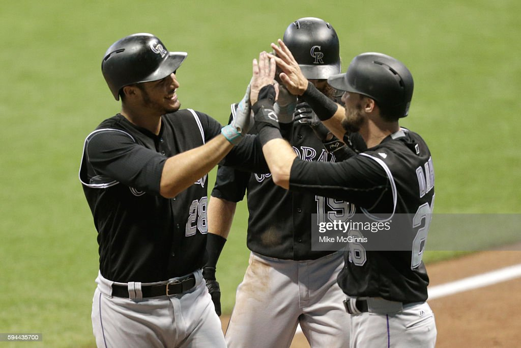 Nolan Arenado of the Colorado Rockies celebrates with David Dahl and Charlie Blackmon after hitting a three run homer during the third inning against...