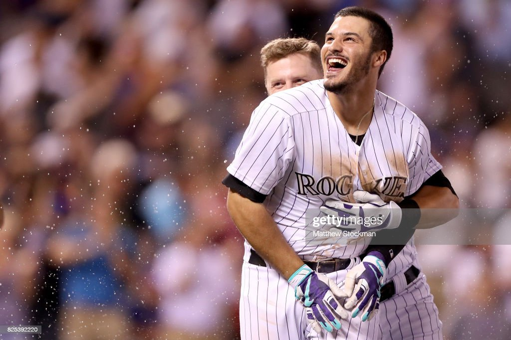 Nolan Arenado #28 of the Colorado Rockies celebrates with Mark Reynolds #12 after driving in the game winning run in the ninth inning against the New York Mets at Coors Field on August 1, 2017 in Denver, Colorado.