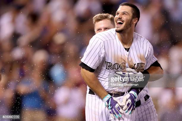 Nolan Arenado of the Colorado Rockies celebrates with Mark Reynolds after driving in the game winning run in the ninth inning against the New York...