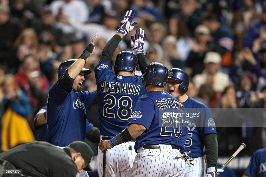 Nolan Arenado #28 of the Colorado Rockies celebrates with Michael Cuddyer #3, Wilin Rosario #20, and Wilin Rosario #20 after hitting a grand slam home run in the seventh inning of a game against the Tampa Bay Rays at Coors Field on May 4, 2013 in Denver, Colorado.