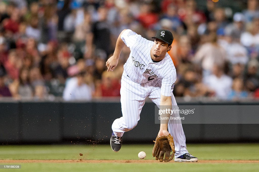<a gi-track='captionPersonalityLinkClicked' href=/galleries/search?phrase=Nolan+Arenado&family=editorial&specificpeople=7934273 ng-click='$event.stopPropagation()'>Nolan Arenado</a> #28 of the Colorado Rockies fields a ground ball in the seventh inning of a game against the Cincinnati Reds at Coors Field on August 31, 2013 in Denver, Colorado. The Reds beat the Rockies 8-3.