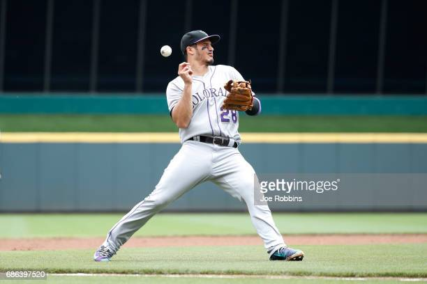 Nolan Arenado of the Colorado Rockies gets hit in the face trying to field the ball in the first inning of a game against the Cincinnati Reds at...