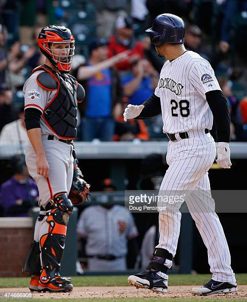 Nolan Arenado of the Colorado Rockies has words with catcher Buster Posey of the San Francisco Giants as he scores on his three run home run off of...