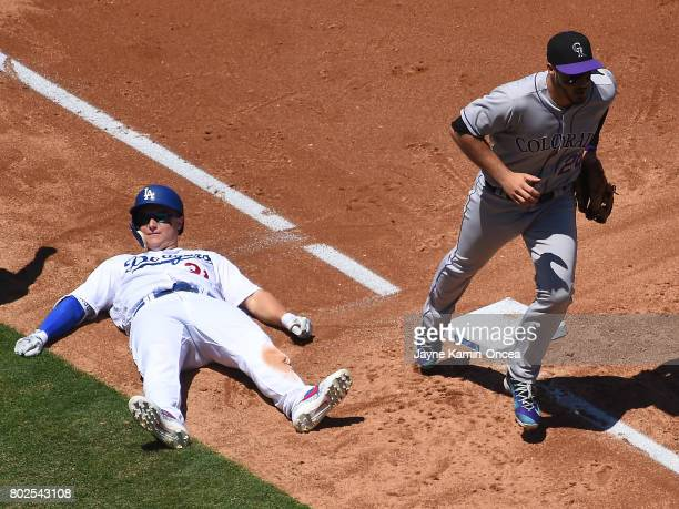 Nolan Arenado of the Colorado Rockies heads back to the dugout as Joc Pederson of the Los Angeles Dodgers lays on the ground after he was is tagged...