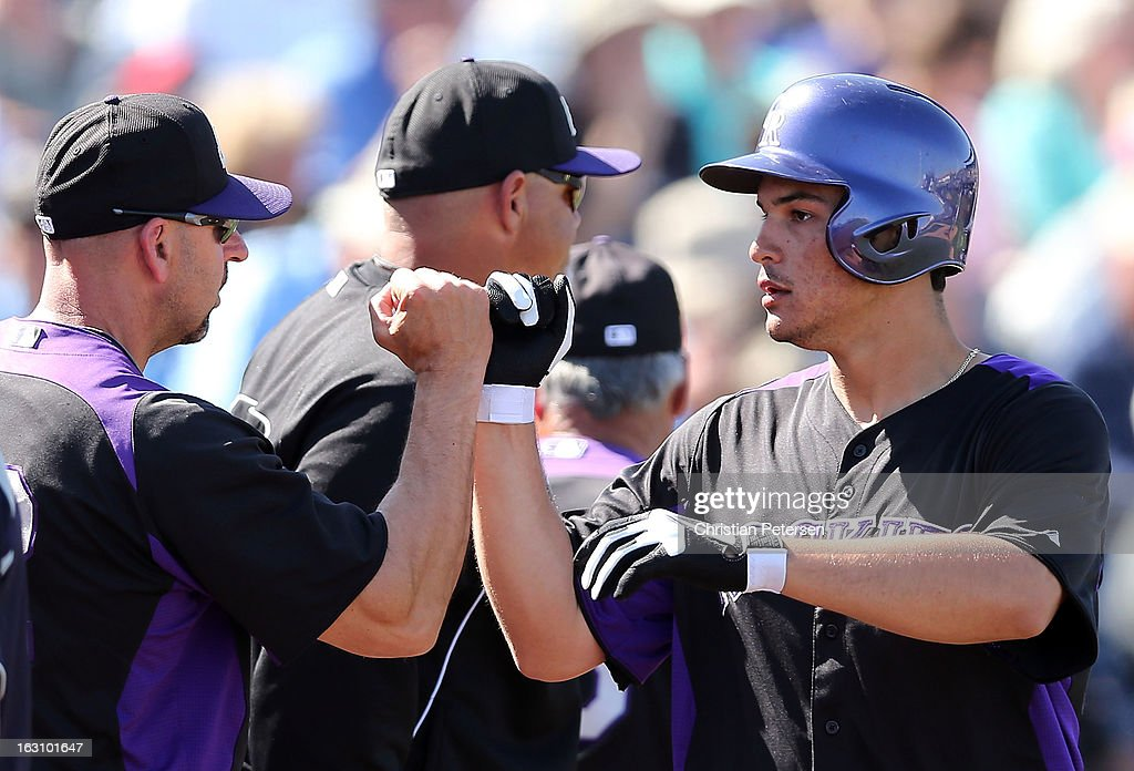 Nolan Arenado #28 of the Colorado Rockies high fives manager <a gi-track='captionPersonalityLinkClicked' href=/galleries/search?phrase=Walt+Weiss&family=editorial&specificpeople=239045 ng-click='$event.stopPropagation()'>Walt Weiss</a> after Arenado hit a solo home run against the Seattle Mariners during the fourth inning of the spring training game at Peoria Stadium on March 4, 2013 in Peoria, Arizona.